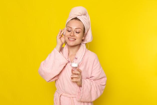 Una giovane bella femmina di vista frontale in accappatoio rosa che pulisce tutto il suo fronte con il pulitore Foto Gratuite