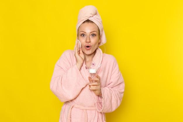 Una giovane bella femmina di vista frontale in accappatoio rosa che pulisce tutto il trucco con il pulitore Foto Gratuite