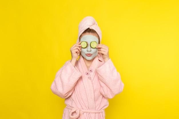 Una giovane bella femmina di vista frontale in accappatoio rosa che tiene le fette di cetriolo Foto Gratuite