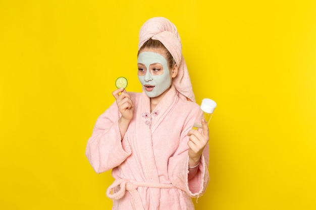 A front view young beautiful female in pink bathrobe holding spray and cucumber Free Photo