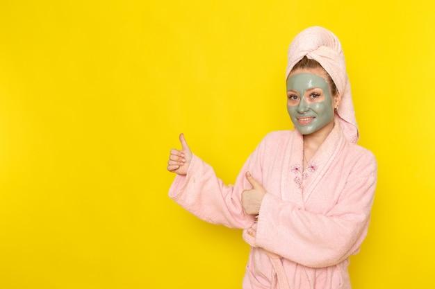 Una giovane bella femmina di vista frontale in accappatoio rosa che sorride e che posa Foto Gratuite