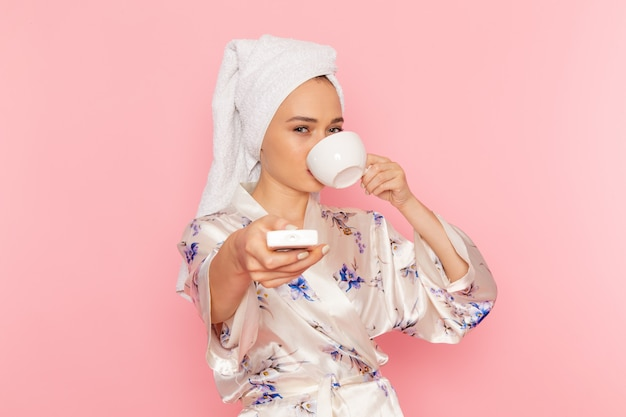 Una giovane donna bella vista frontale in accappatoio, bere caffè e spegnere l'aria condizionata Foto Gratuite
