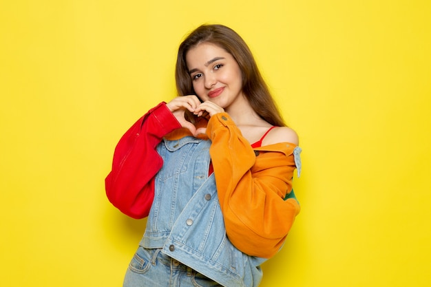 A front view young beautiful lady in red shirt colorful coat and blue jeans showing heart sign model girl color female Free Photo