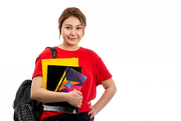 A front view young beautiful lady in red t-shirt black jeans smiling holding different copybooks and files with bag on the white Free Photo
