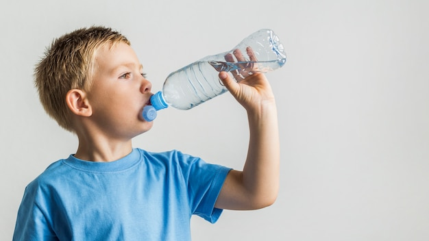 Front view young boy drinking water Free Photo