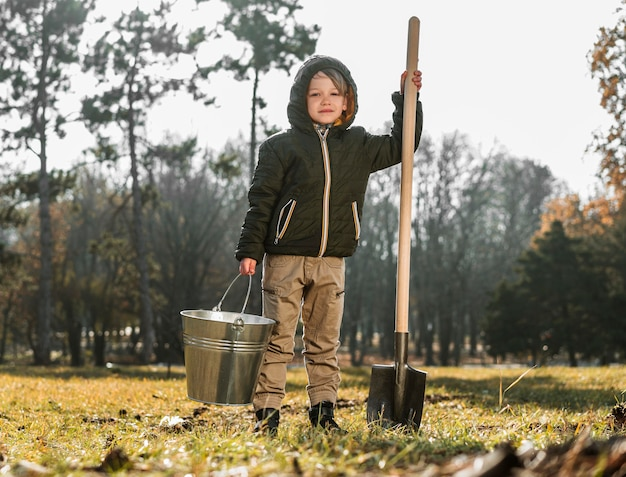 Front view of young boy outdoors holding bucket and shovel Free Photo