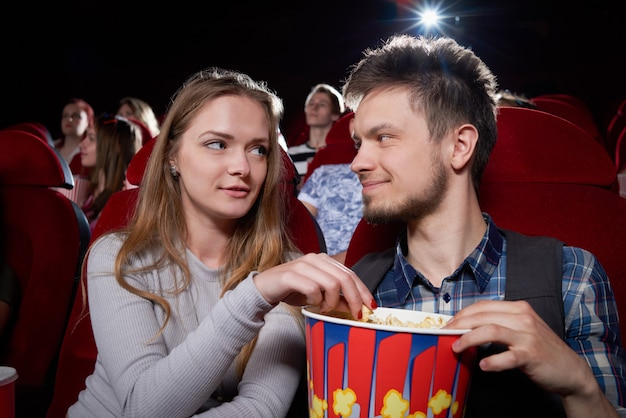 Front view of young couple eating popcorn and looking each other face to face during comedy in cinema theater. blonde girl and handsome man having romantic date and enjoying funny movie. Premium Photo