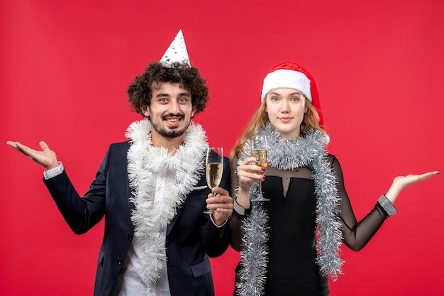 赤い机の写真で新年を祝うばかりの若いカップルの正面図クリスマスの愛 無料写真