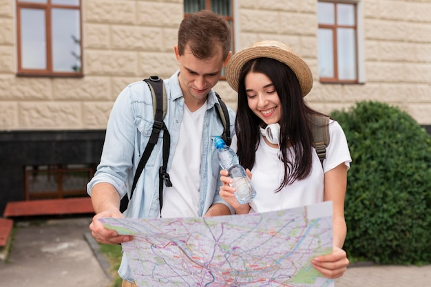 Front view young couple looking at the map Premium Photo