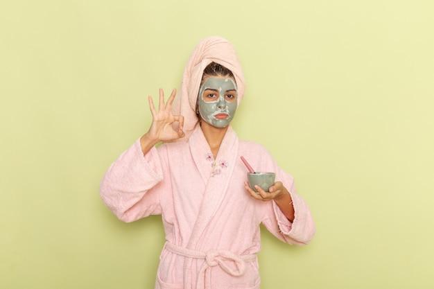 緑の机の上にマスクを適用ピンクのバスローブでシャワーを浴びた後の正面図若い女性 無料写真