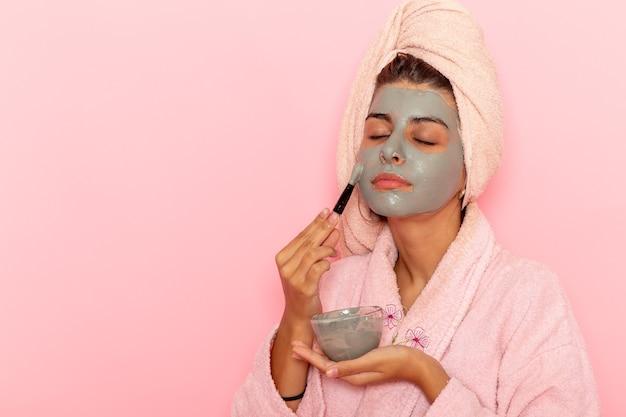 ピンクの表面にマスクを適用ピンクのバスローブでシャワーを浴びた後の正面図若い女性 無料写真