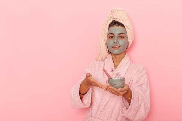 淡いピンクの表面にマスクを適用するピンクのバスローブでシャワーを浴びた後の正面図若い女性 無料写真