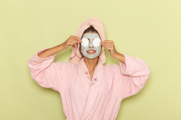 Giovane femmina di vista frontale dopo la doccia in accappatoio rosa che copre gli occhi con cotone sulla superficie verde Foto Gratuite