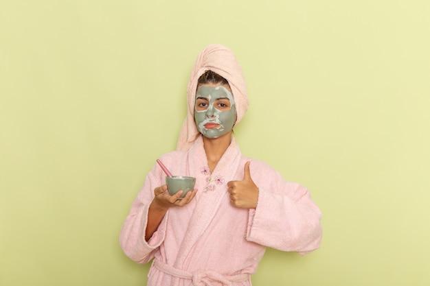 Giovane femmina di vista frontale dopo la doccia in ciotola rosa della tenuta dell'accappatoio con la maschera su una superficie verde Foto Gratuite