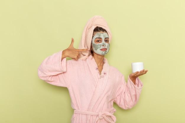 Giovane femmina vista frontale dopo la doccia in accappatoio rosa che tiene crema sulla superficie verde Foto Gratuite