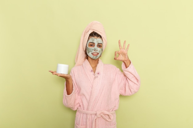 Giovane femmina di vista frontale dopo la doccia in accappatoio rosa che tiene crema e sorridente su una superficie verde Foto Gratuite