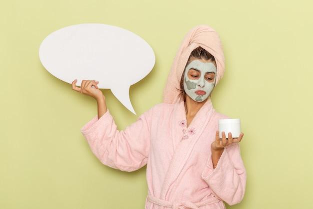 Giovane femmina di vista frontale dopo la doccia in accappatoio rosa che tiene crema e segno bianco sulla superficie verde Foto Gratuite