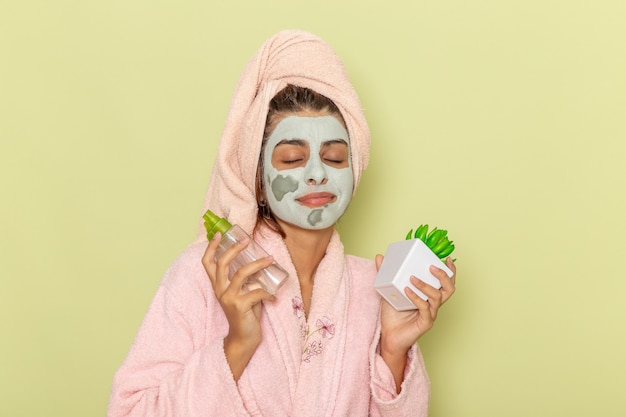Front view young female after shower in pink bathrobe holding make-up removers on green floor cream mask shower selfcare beauty bath Free Photo