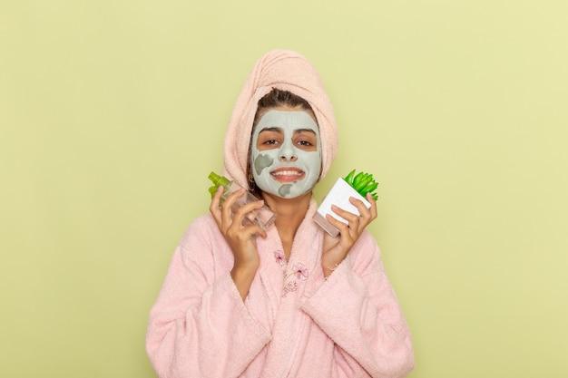Giovane femmina di vista frontale dopo la doccia in accappatoio rosa che tiene gli struccanti sorridente sulla superficie verde Foto Gratuite