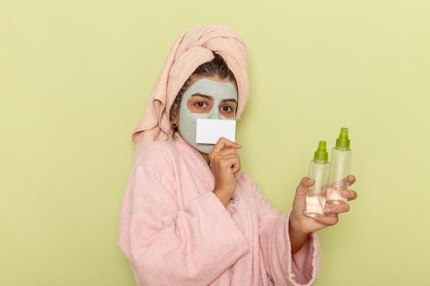 Giovane femmina di vista frontale dopo la doccia in accappatoio rosa che tiene gli spray e la carta sulla superficie verde chiaro Foto Gratuite