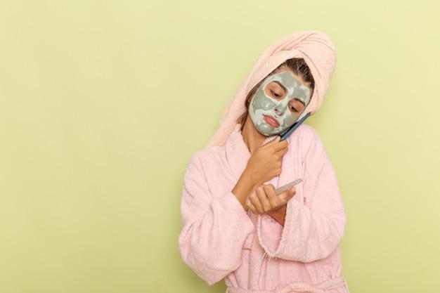 Giovane femmina di vista frontale dopo la doccia in accappatoio rosa, parlando al telefono sulla superficie verde chiaro Foto Gratuite
