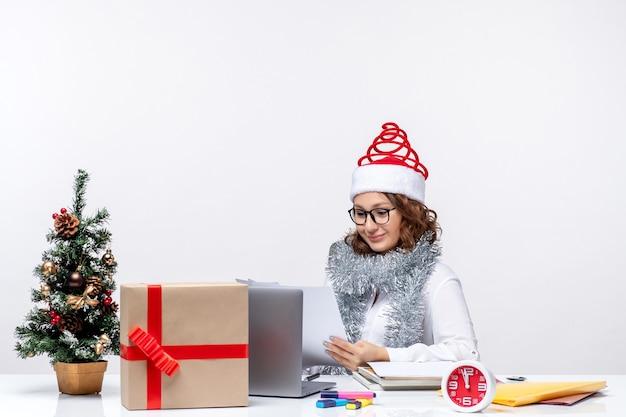 白い背景の上のドキュメントで作業職場で若い女性の正面図 無料写真