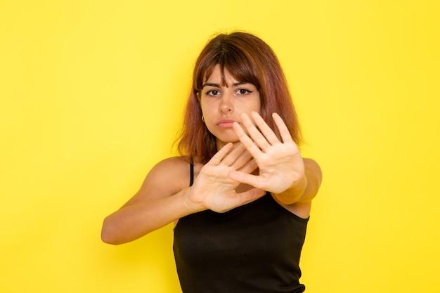 Vista frontale della giovane donna in camicia nera e jeans grigi prudenti sulla parete gialla Foto Gratuite