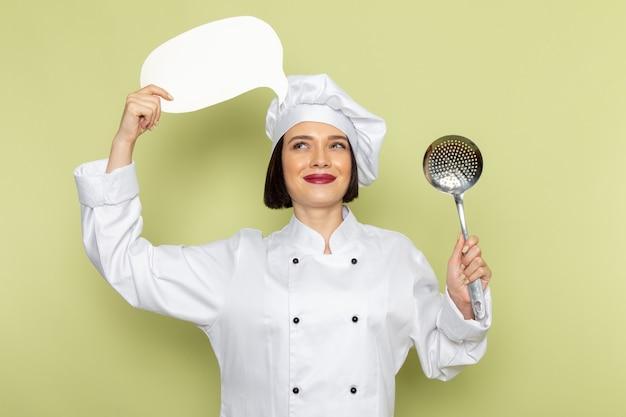 Una giovane cuoca femminile di vista frontale in vestito bianco del cuoco e cappuccio che tiene il cucchiaio e segno bianco sul colore della cucina dell'alimento del lavoro della signora della parete verde Foto Gratuite