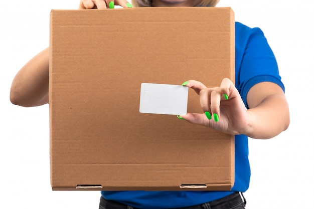 Un giovane corriere femminile di vista frontale in pacchetto di consegna dell'alimento della tenuta uniforme blu e carta bianca Foto Gratuite