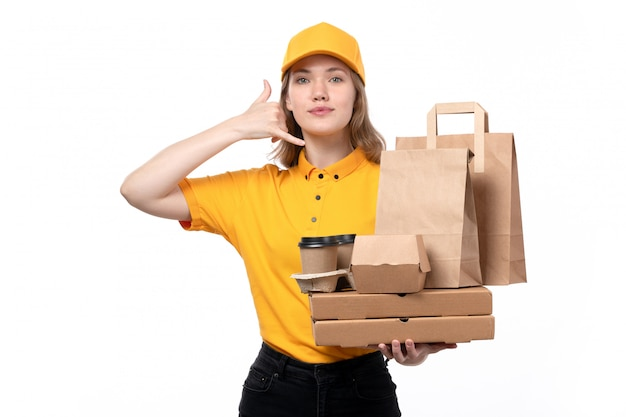 A front view young female courier female worker of food delivery service holding coffee cups food packages showing phone call sign on white Free Photo
