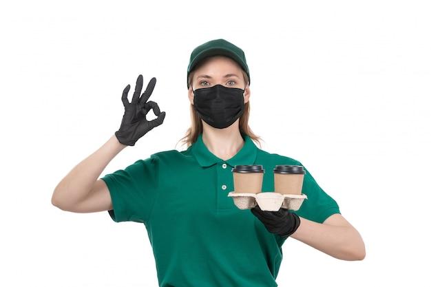 Un giovane corriere femminile di vista frontale in guanti neri uniformi verdi e mascherina nera che tengono le tazze di caffè Foto Gratuite