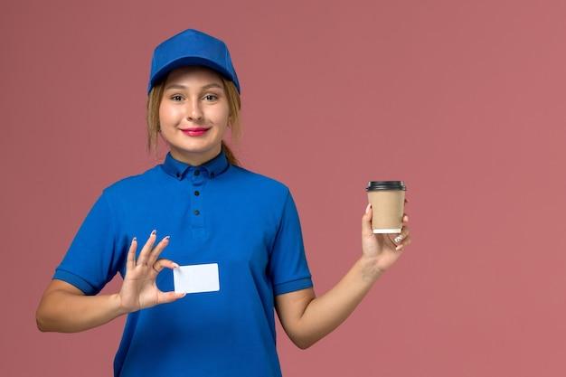 正面図青い制服の若い女性の宅配便は、茶色のコーヒーの配達カップを保持しているポーズ、サービス制服配達女性の仕事 無料写真