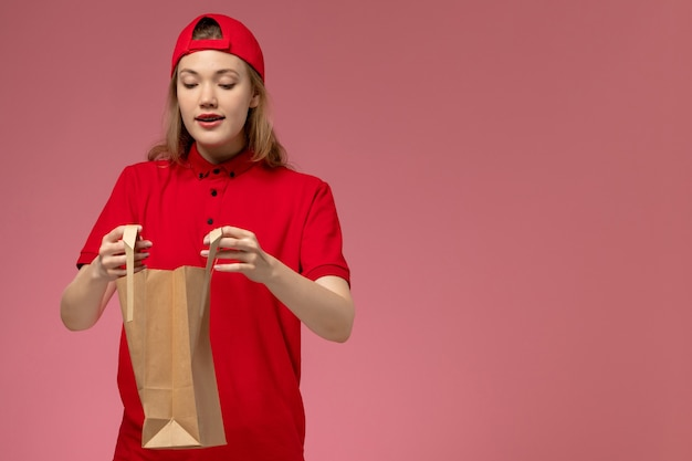 Вид спереди молодая женщина-курьер в красной форме и накидке, держащая посылку с доставкой на розовой стене Бесплатные Фотографии