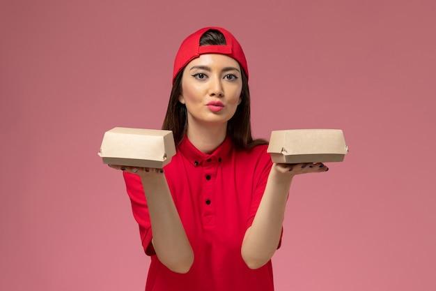 ピンクの壁に彼女の手に小さな配達食品パッケージと赤い制服とケープの正面図若い女性の宅配便 無料写真