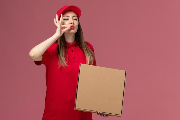 淡いピンクの背景に配達フードボックスを保持している赤い制服の正面図若い女性の宅配便サービス配達制服会社 無料写真