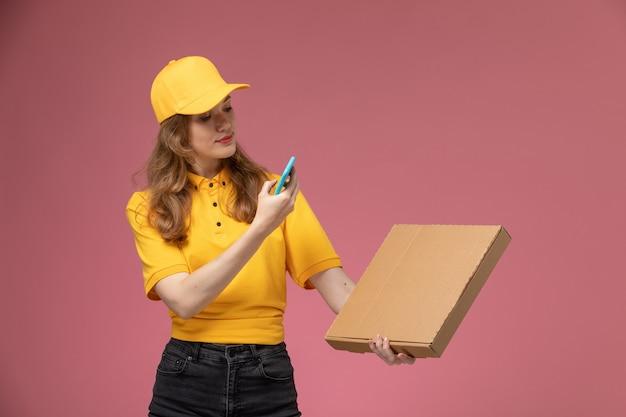 ピンクの背景の机の上の食品とパッケージの写真を撮る黄色の制服を着た若い女性の宅配便の正面図仕事制服配達サービスワーカー 無料写真