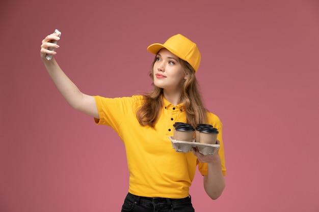 진한 분홍색 배경 유니폼 배달 작업 서비스 색상에 커피와 함께 셀카를 복용 노란색 유니폼 노란색 케이프에서 전면보기 젊은 여성 택배 무료 사진