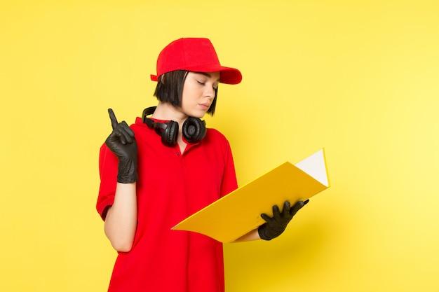 Un giovane corriere femminile di vista frontale in guanti neri uniformi rossi e spiritello malevolo che tengono archivio giallo Foto Gratuite