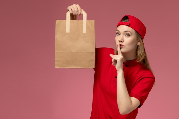 Front view young female courier in red uniform and cape holding delivery food package on light-pink wall Free Photo