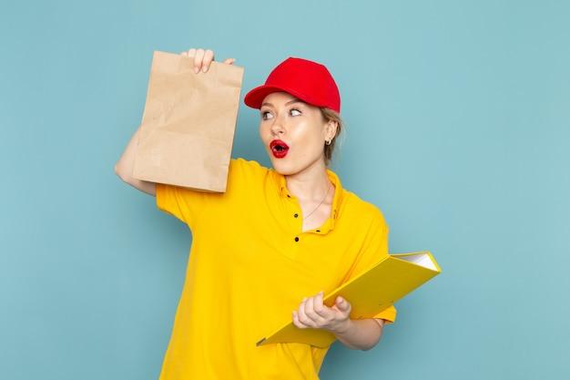 Giovane corriere femminile di vista frontale in pacchetto rosso della tenuta del mantello della camicia gialla e archivio giallo sul lavoratore dello spazio blu Foto Gratuite