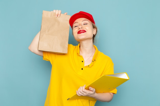Giovane corriere femminile di vista frontale in camicia gialla e pacchetto rosso della tenuta del capo e archivio giallo che sorride sull'operaio blu dello spazio Foto Gratuite