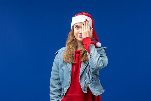 Giovane femmina di vista frontale che copre metà del suo viso su sfondo blu colore di emozione di natale Foto Gratuite