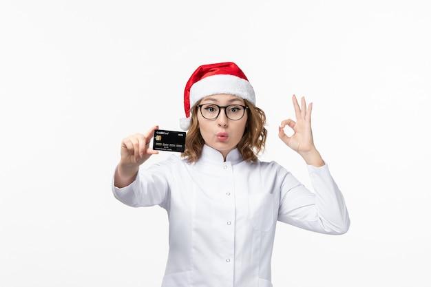 흰색 책상 돈 간호사 새 해에 은행 카드를 들고 전면보기 젊은 여성 의사 무료 사진