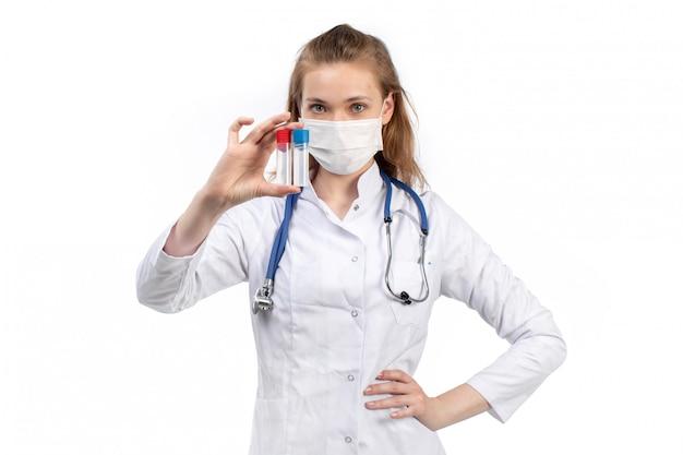 Un giovane medico femminile di vista frontale in vestito medico bianco con lo stetoscopio che indossa maschera protettiva bianca che posa le boccette della tenuta sul bianco Foto Gratuite