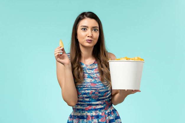 Front view young female eating cips and watching movie on the blue surface Free Photo