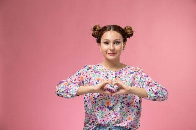 Vista frontale giovane femmina in camicia fiore progettato sorridente che mostra il segno del cuore su sfondo rosa Foto Gratuite