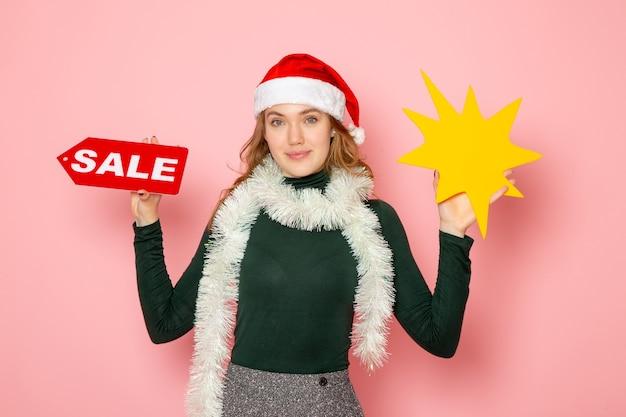 正面図若い女性が大きな黄色の図を保持し、淡いピンクの壁の色の休日のクリスマス新年の感情に販売を書いています 無料写真