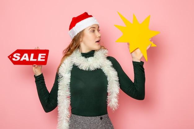 正面図ピンクの壁の色モデルの休日のクリスマスの新年の感情に大きな黄色の図と販売の書き込みを保持している若い女性 無料写真