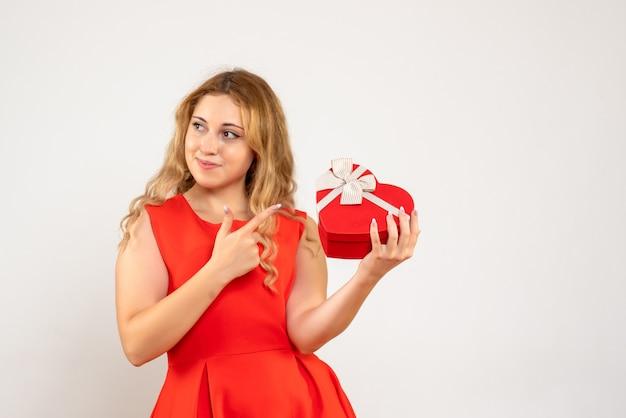 Вид спереди молодая женщина держит подарок в форме сердца Бесплатные Фотографии