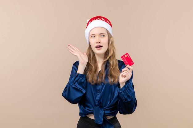 분홍색 배경 돈 사진 휴가 새 해 크리스마스 감정에 빨간 은행 카드를 들고 전면보기 젊은 여성 무료 사진